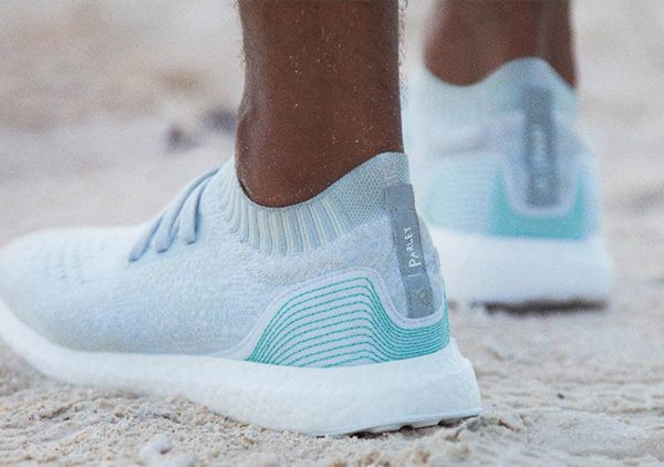 Adidas and Parley blue and white running shoes on sand