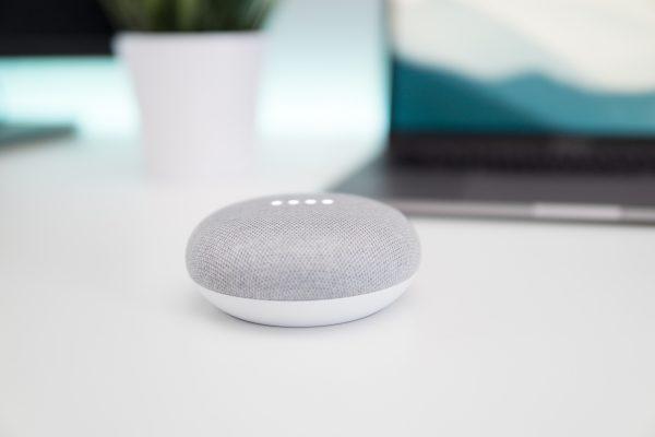 Google mini on a white table.