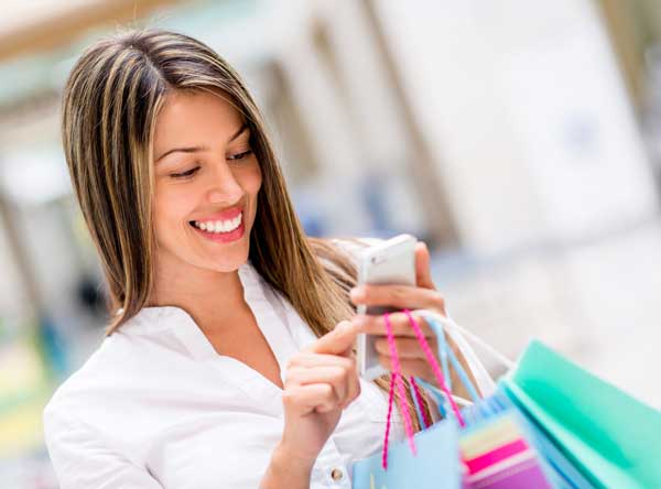 Happy woman using cell phone at a shopping center