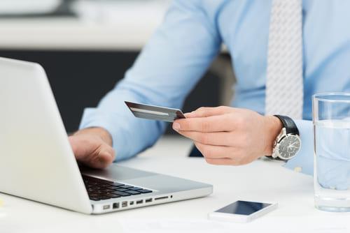Man holding credit card while browsing his laptop.