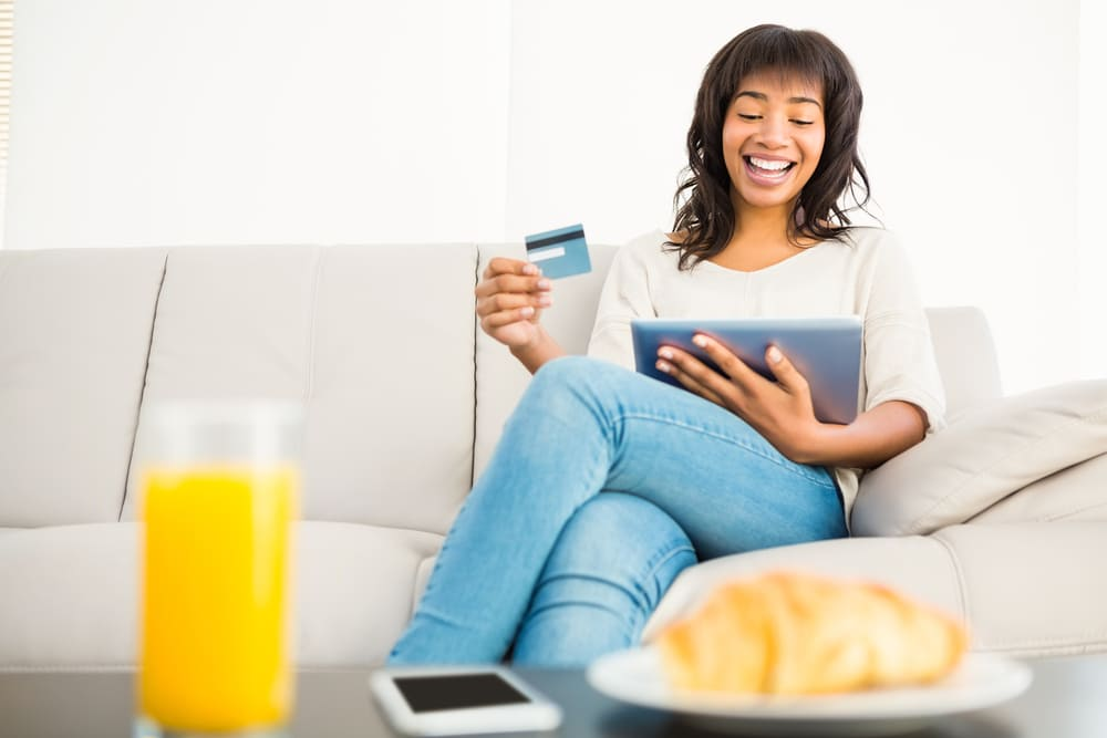 Woman on a couch, holding a tablet and a credt card in her hand.