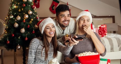 Image of three people in front of a Christmas tree, eating popcorn and holding a remote control.