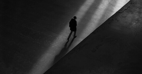 Person walking down a dark hallway, heading towards a stream of light.