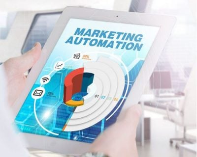 Graphic of a person holding a tablet, which says Marketing Automation on the screen.
