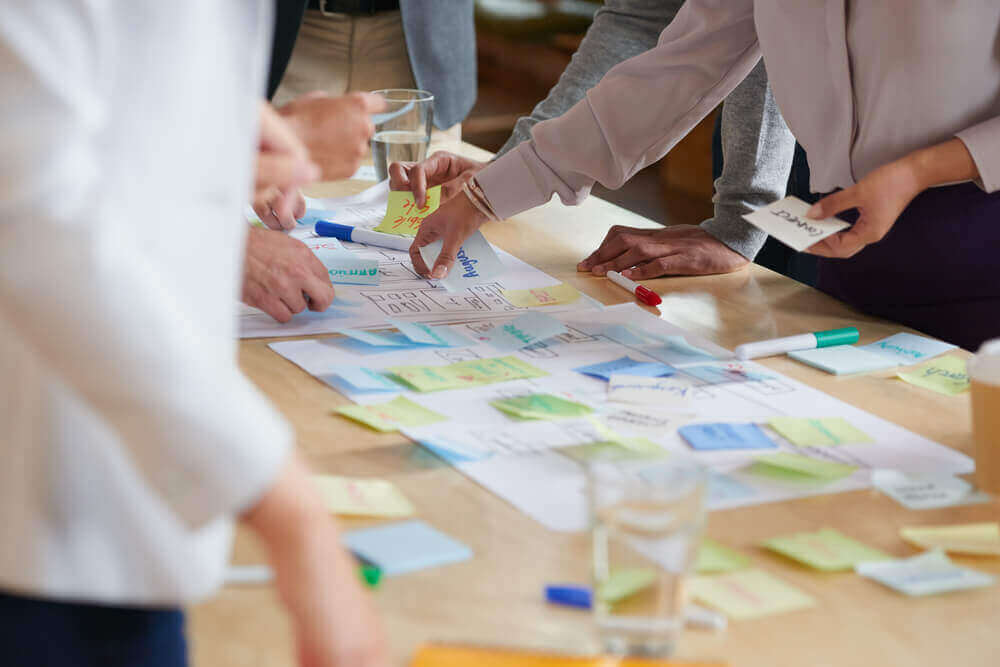 Image of people standing over a long table, with a lot of sticky notes stuck on it.