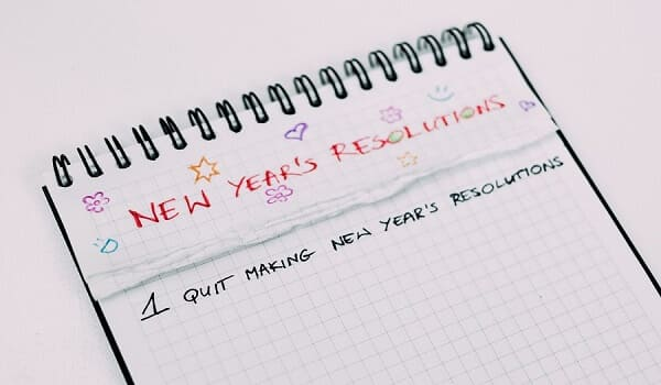Image of a notebook, with New Year's Resolutions written on top of the page.