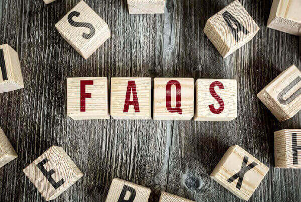 Wooden blocks on a grey table with the word FAQs.